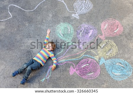 Cute little kid boy playing and flying with colorful balloons picture drawing with chalk. Creative leisure for children outdoors in summer, celebrating birthday - stock photo