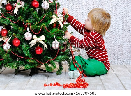 Cute little kid decorating Christmas tree with red beads - stock photo
