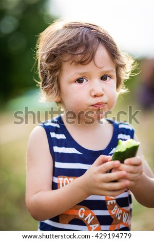 Cute little kid eating a cucumber in the garden. Kids eat vegetables outdoors. Healthy snack for children.  - stock photo