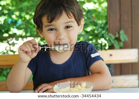 Cute little kid eating ice cream and enjoying - stock photo