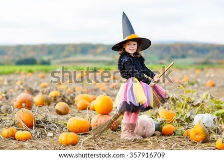 Cute little kid girl wearing halloween witch costume having fun on a pumpkin patch. Traditional family festival with children. Happy child
