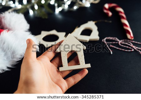 cute little kid hand and beautiful natural christmas toys and silver garland on black background