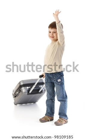 Cute little kid holding baggage waving, smiling. - stock photo