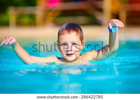 cute little kid swimming in summer pool - stock photo