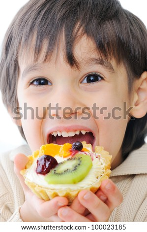 Cute little kid trying out delicous cake - stock photo