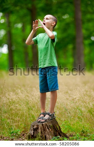 Cute little kid trying to make echo in the forest by shouting - stock photo