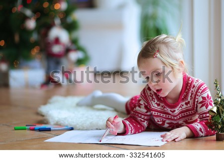 Cute little kid  writes letter to Santa. Adorable toddler girl in festive dress lying on the floor on lambskin carpet. Christmas tree with lights and gifts at the background. - stock photo