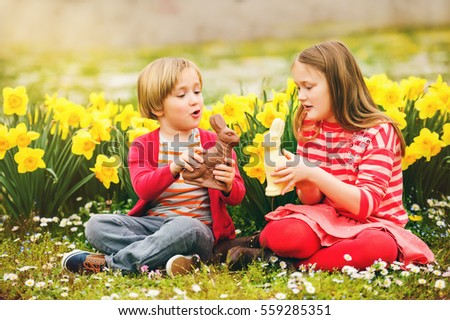 Cute little kids, big sister and small brother, with chocolate Easter bunnies celebrating traditional feast. Family, holiday, spring , carefree childhood concept.