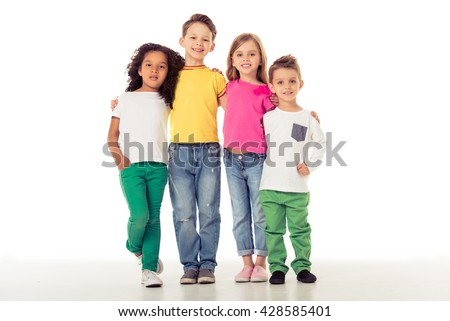 Cute little kids in casual clothes are looking at camera and smiling while standing with their arms around each other, isolated on a white background - stock photo