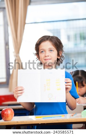 Cute little kindergarten schoolboy holding up a book showing his work. - stock photo