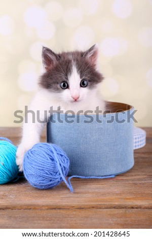 Cute little kitten in box playing with thread ball, on light background