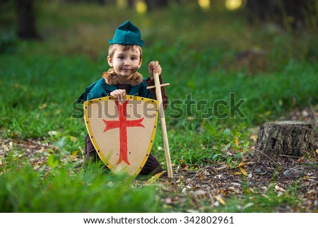 Cute little knight playing in the forest - stock photo