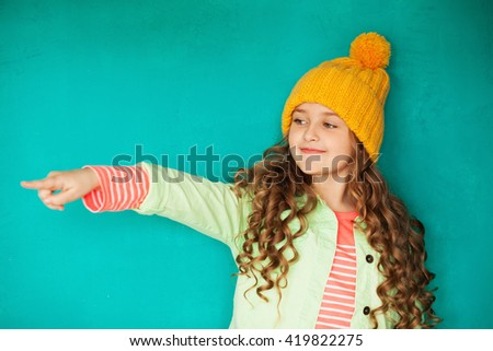 Cute little lady in yellow woolen cap point on something  - stock photo