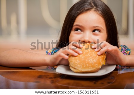 Cute little Latin girl eating a hamburger and looking up towards copy space - stock photo