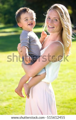 Cute little laughing barefoot toddler in striped shirt being held in arms of smiling mother