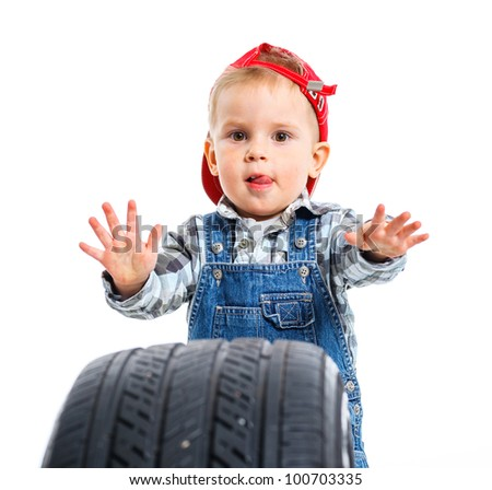 Cute little mechanic with a tire. Isolated on the white backround - stock photo