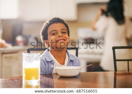cute little mixed race boy smiling into camera with mother in background at breakfast