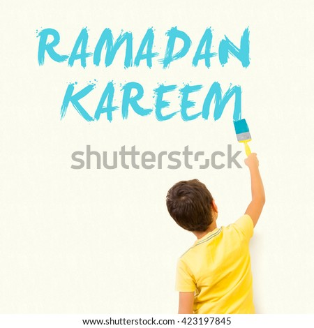 Cute little Muslim kid drawing Ramadan Kareem with painting brush on wall background - stock photo