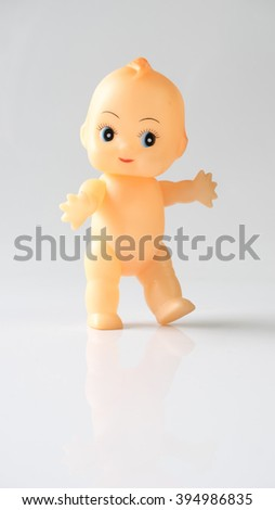 Cute little naked baby doll with blue eyes sitting or walking on empty background. Slightly de-focused and close-up shot. Copy space. - stock photo