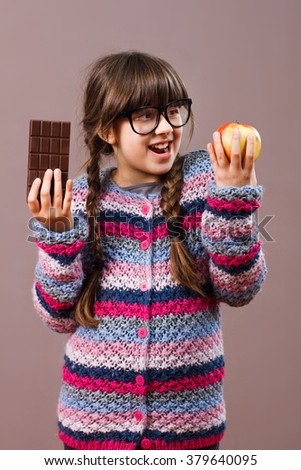 Cute little nerdy girl is holding apple and chocolate in her hands and she has decided to eat healthy.I think that apple is better choice! - stock photo