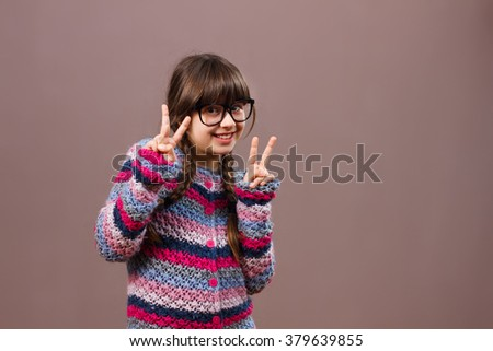 Cute little nerdy girl is showing peace sign.I am for peace!