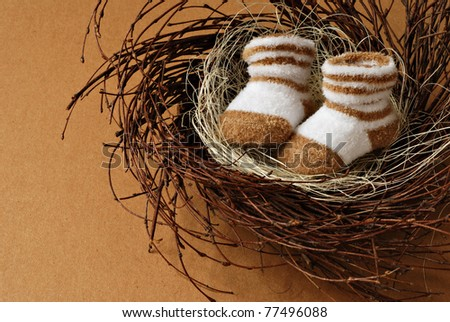 Cute little newborn baby booties in nest on brown paper background with copy space.  Motherhood concept. - stock photo