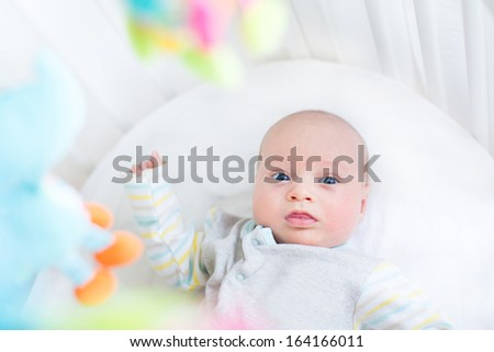 Cute little newborn baby in a white crib with colorful toys - stock photo