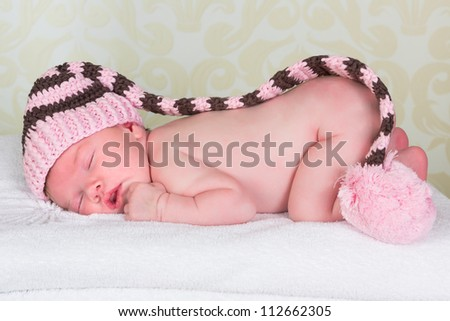 Cute little newborn baby of 11 days old with a pink pompom hat - stock photo
