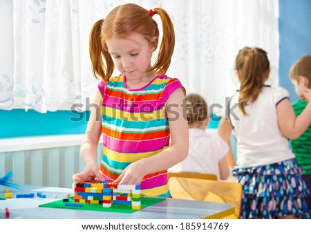 Cute little orange haired girl playing at kindergarten - stock photo