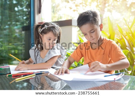 Cute little pan asian boy coloring his drawing while sitting while being watched by his curious younger sister in home environment - stock photo