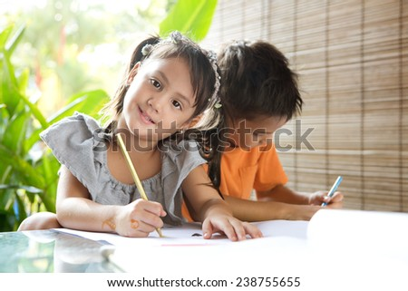 Cute ?little pan asian girl holding a coloring pencil sitting next to an older brother engrossed in coloring activity in home environment - stock photo