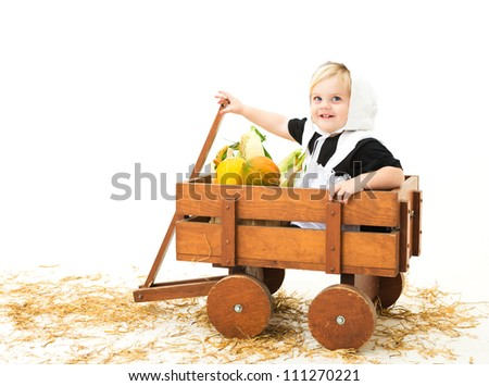 cute little pilgrim girl in a wagon full of Fall vegetables - stock photo