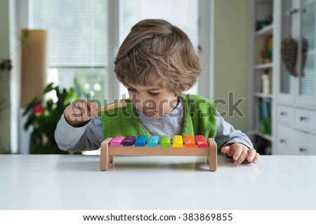 Cute little playing on xylophone. Musical education, help recognise musical talent, how to support and encourage children's creativity