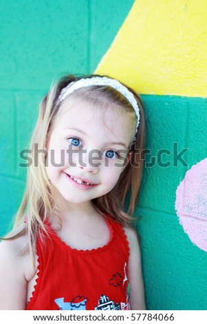 Cute little preschool age girl stands outside a school building waiting to attend school. - stock photo