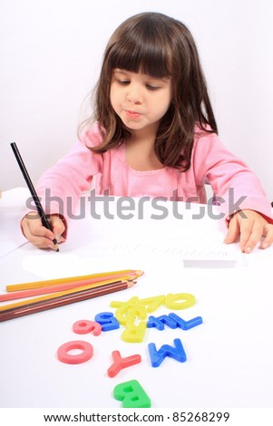Cute little preschool girl playing with letters and drawing with pencils on white - stock photo