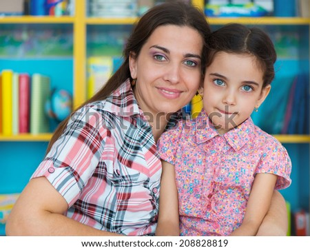 Cute little preschool girl with her mother at home - stock photo