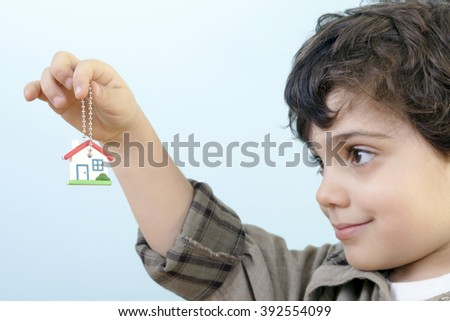 Cute little preschooler boy is showing and offering us a new house's keys against blue background. - stock photo