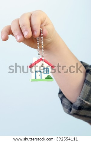 Cute little preschooler boy is showing and offering us a new house's keys against blue background.