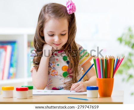 Cute little preschooler child drawing at home - stock photo