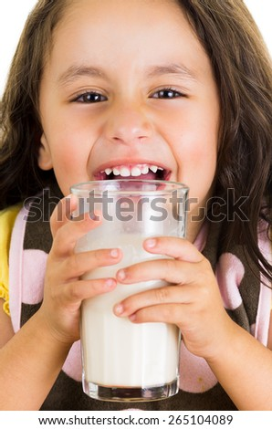 Cute little preschooler girl drinking a glass of milk isolated on white - stock photo