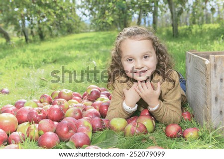 Cute little preschooler girl eating an apple on beautiful autumn day - stock photo