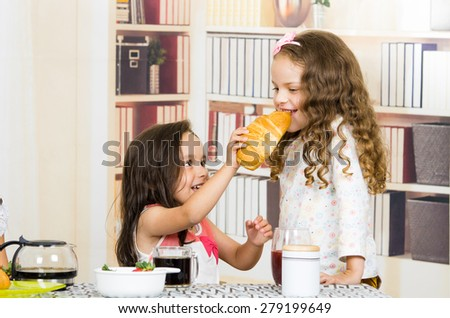 Cute little preschooler girl feeding bread to her sister - stock photo