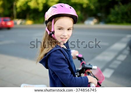 Cute little preschooler girl riding a bike in a city wearing helmet on summer day - stock photo
