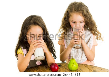 Cute little preschooler girls drinking milk and eating fruits for snack isolated on white - stock photo