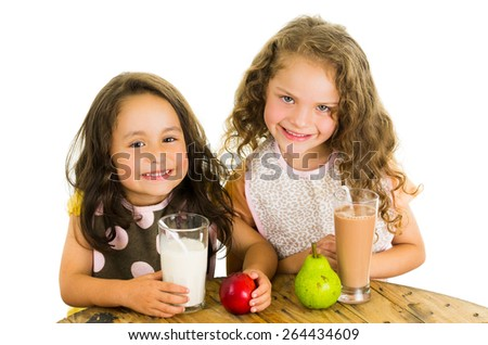 Cute little preschooler girls drinking milk and eating fruits isolated on white - stock photo