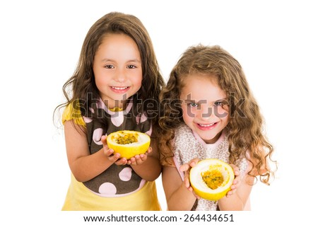 Cute little preschooler girls holding a cut open passion fruit isolated on white