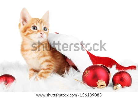 Cute little red kitten in Santa hat isolated on white - stock photo