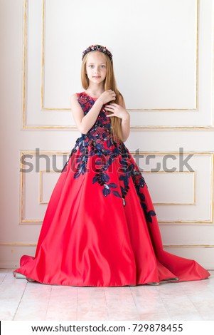 Cute little redhead girl wearing an antique princess dress or costume