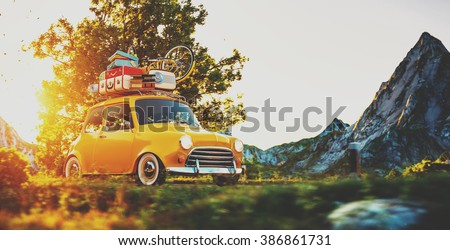 Cute little retro car with suitcases and bicycle on top goes by wonderful countryside road at sunset - stock photo