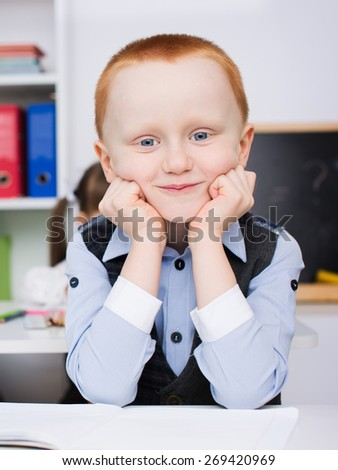 cute little schoolboy in classroom at lesson - stock photo